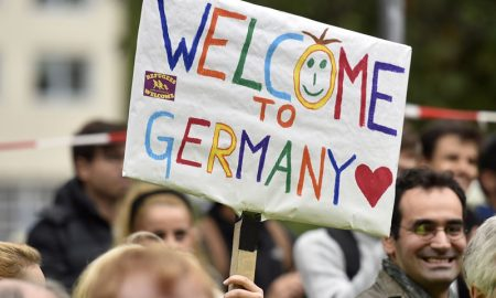People welcome refugees with a banner reading 'welcome to Germany' in Dortmund, Germany, Sunday, Sept. 6, 2015, where thousands of migrants and refugees arrived by trains. (AP Photo/Martin Meissner)
